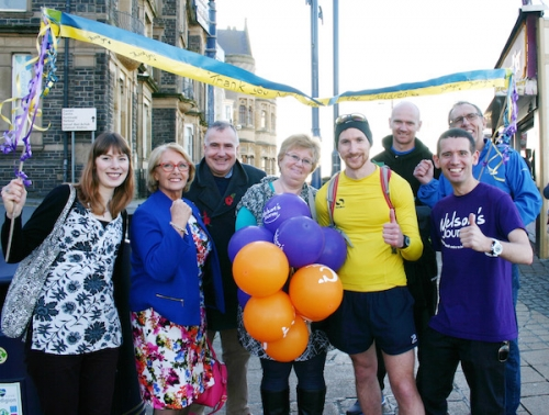 Photo of Matt Roberts at the 'finish line' of Aberystwyth Pier. Pictured [L-R]: Claudia Milburn (friend from Norfolk), Cllr Mair Benjamin (Aberystwyth councillor); Mark Williams MP for Ceredigion; Julie Roberts (mother); Matt Roberts; Dan Roberts (brother); Simon Wright (CEO of Nelson's Journey); Ian Roberts (father)