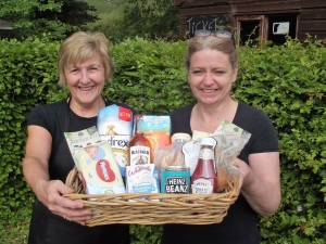 Sally Randell and Michelle Philpott from Fairhaven tearoom with a basket featuring some of the provisions.
