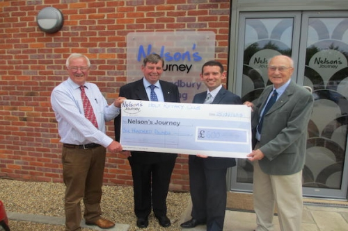 (L-R) John Sizeland, John Richley and Frank Fidgeon present the cheque to Nelson's Journey CEO Simon Wright (second right) outside Smiles House.